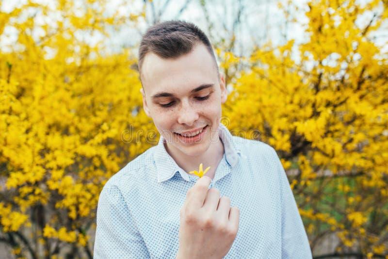 Den lyckliga le romantiska unga mannen med vårguling blommar på trädgården royaltyfri foto