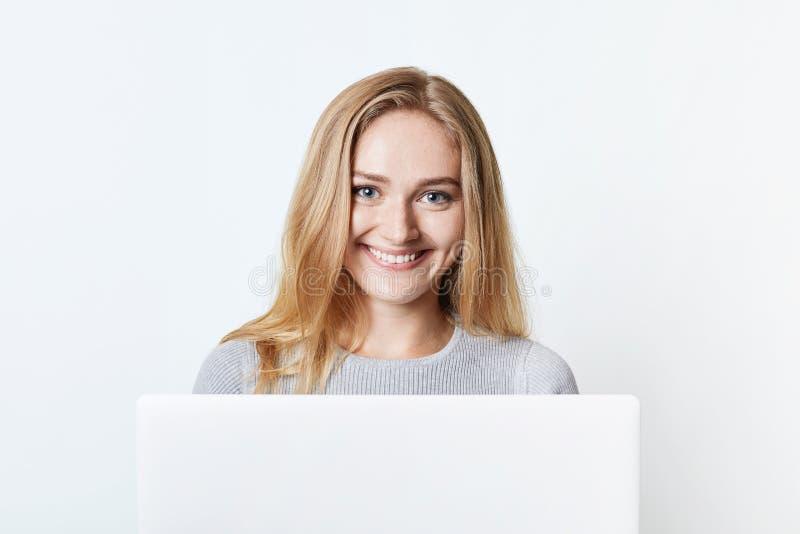 Den lyckliga le självständiga kvinnan arbetar hemma, sitter framme av den öppnade bärbara datorn, tycker om fri trådlös internetu arkivbilder