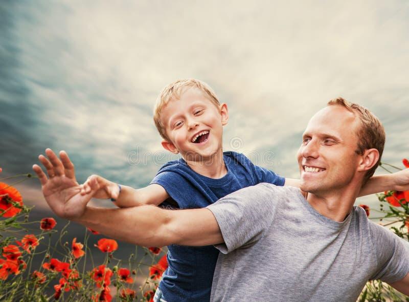 Den lyckliga le sonen med fadern bland vallmo blommar royaltyfria foton
