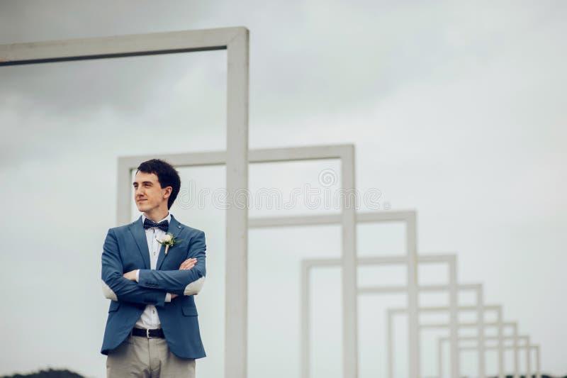 Den lyckliga le stiliga skäggiga brudgummen i blått passar att se fotografering för bildbyråer