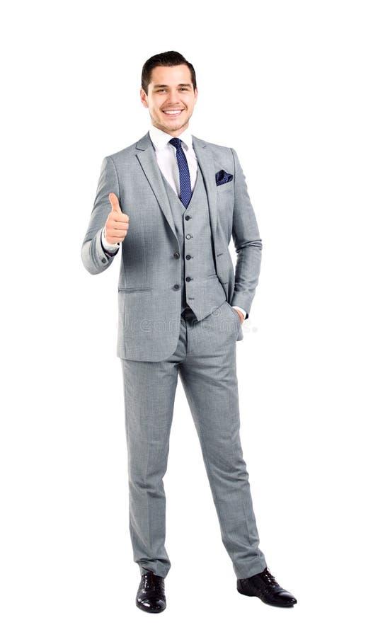 Den lyckliga le unga affärsmanen med tum göra en gest upp royaltyfri foto