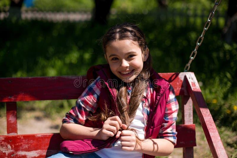 Den lyckliga le unga flickan på gunga parkerar in arkivfoto