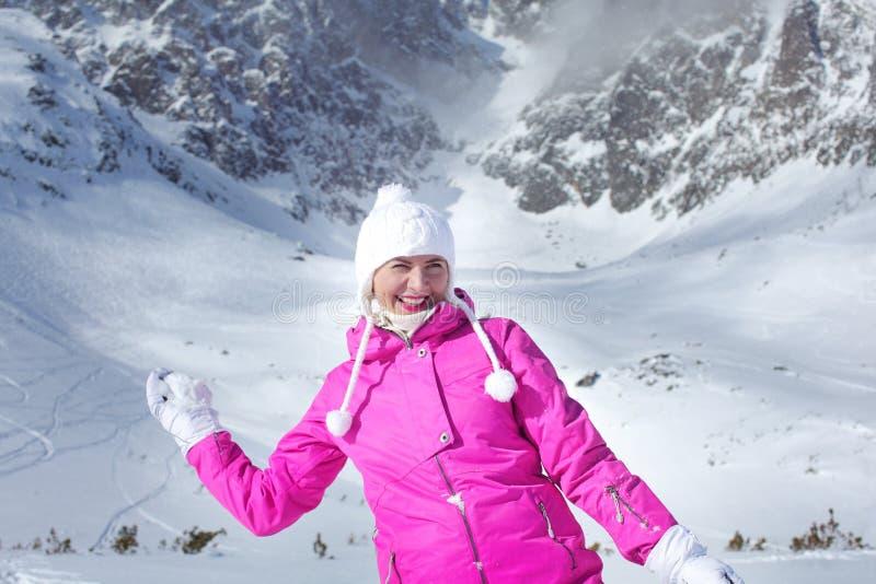Den lyckliga le unga kvinnan i rosa färger skidar omslaget som förbereder sig att kasta royaltyfri fotografi