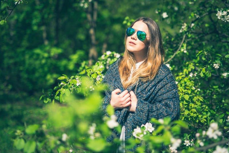 Den lyckliga le unga kvinnan i solglasögon och ett stuckit omslag som tycker om våren, blommar i trädgården royaltyfria bilder