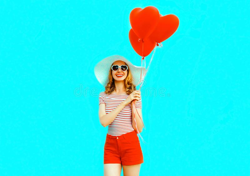 Den lyckliga le unga kvinnan med röd hjärta formade luftballonger i sommarsugrörhatt och kortslutningar på färgrikt royaltyfria foton