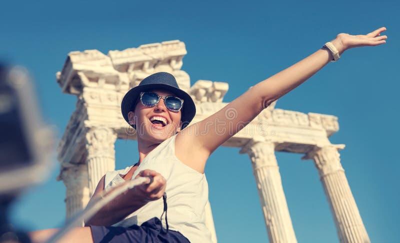 Den lyckliga le unga kvinnan tar ett selfiefoto på antika sikt fotografering för bildbyråer
