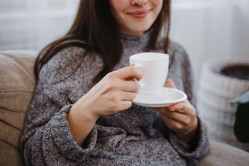 Den lyckliga le unga kvinnan tycker om morgonkaffe royaltyfri fotografi
