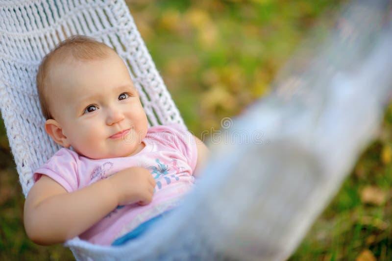 Den lyckliga le ungen, lögner i en hängmatta i aftonen parkerar royaltyfri bild