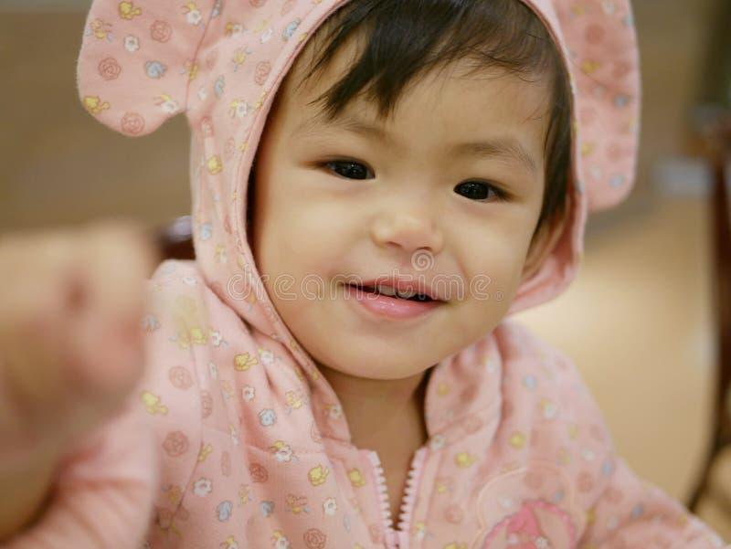 Den lyckliga lilla asiatet behandla som ett barn flickan, 17 gamla som månader ler på en kamera royaltyfri foto