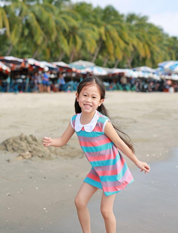 Den lyckliga lilla asiatiska barnflickan har gyckel p? sandstranden p? ferie arkivfoton
