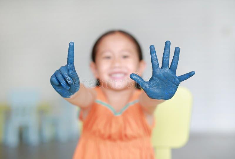 Den lyckliga lilla asiatiska flickan med hennes blåa händer målade uppvisning av en och fem fingrar i ungerum fotografering för bildbyråer