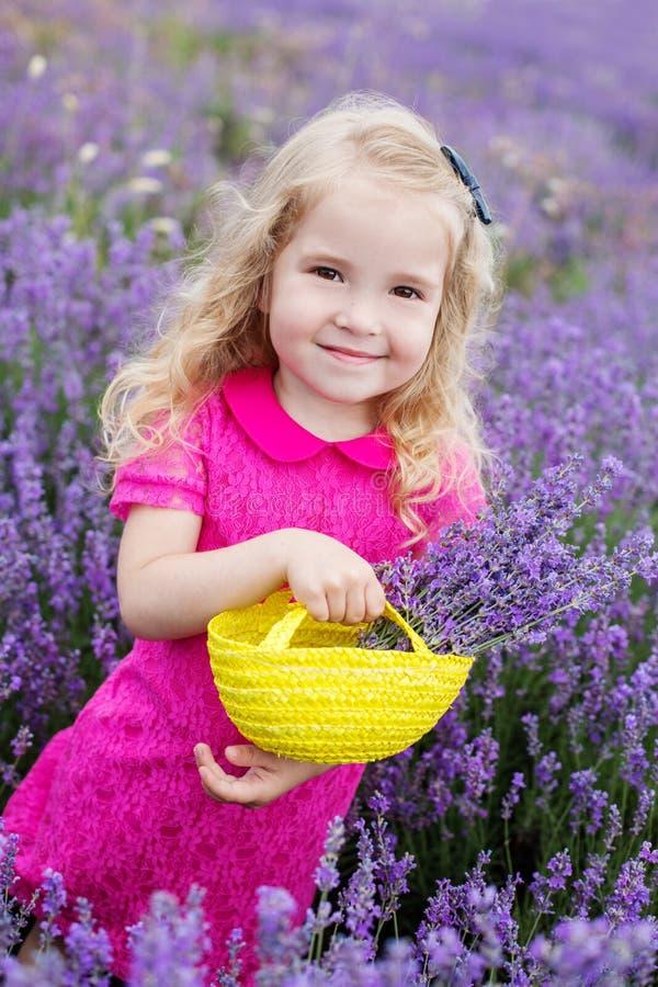 Den lyckliga lilla flickan är i ett lavendelfält arkivbilder