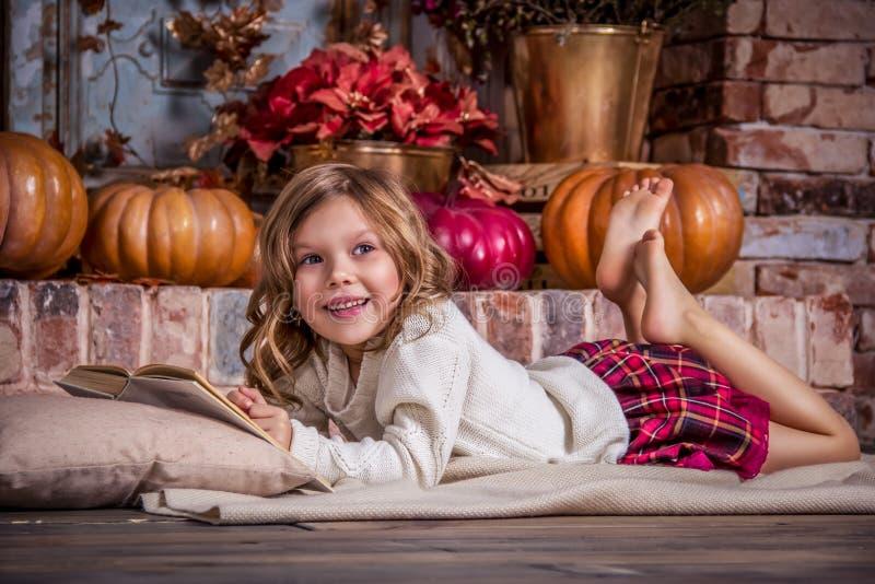 Den lyckliga lilla flickan är läseboken Lycklig liten flicka och pumpa royaltyfri bild