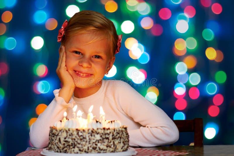 Den lyckliga lilla flickan blåser ut stearinljusen på kakan royaltyfri foto