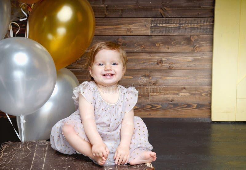Den lyckliga lilla flickan firar hennes första födelsedagparti med ballonger arkivfoto