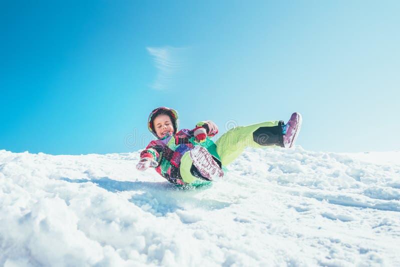 Den lyckliga lilla flickan glider ner från snölutningen Tycka om arkivbild