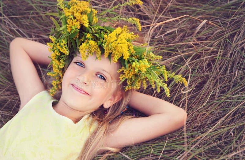 Den lyckliga lilla flickan i blommor krönar att lägga på gräset arkivbild