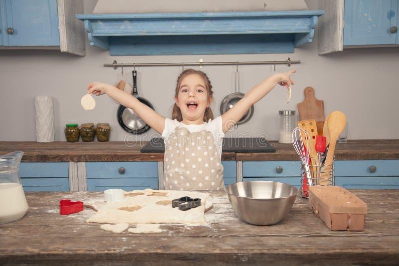 Den lyckliga lilla flickan i köket gör olika former av kakor ut ur deg som hjälper hennes mamma hj arkivbilder