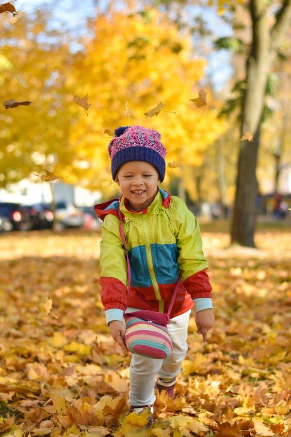 Den lyckliga lilla flickan i ljus kläder som spelar med sidor i en stad, parkerar i hösten fotografering för bildbyråer