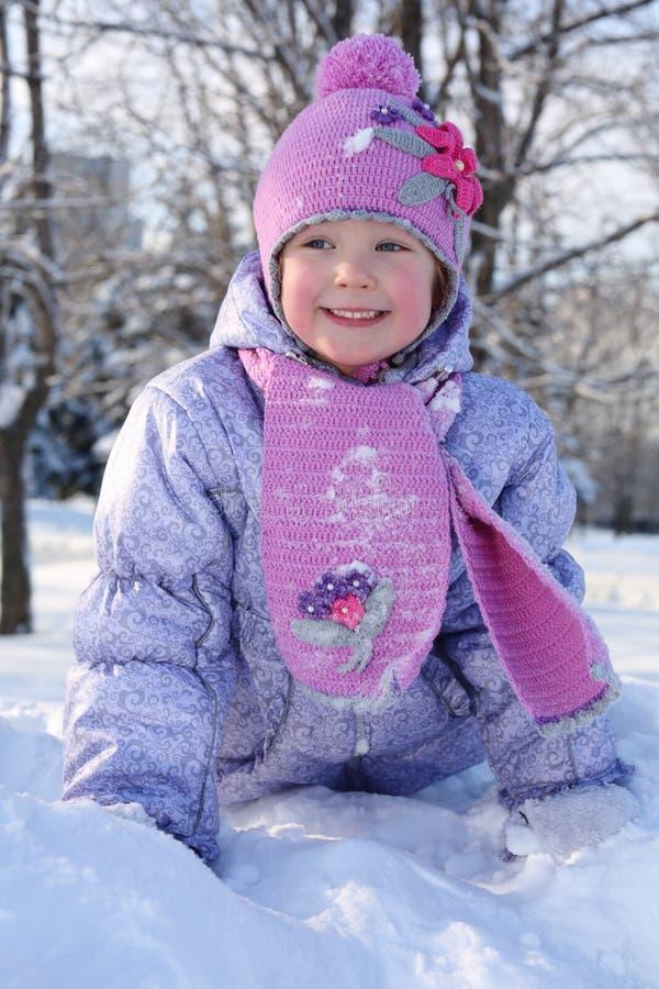Den lyckliga lilla flickan i rosa halsduk och hatt kryper i snö arkivfoton