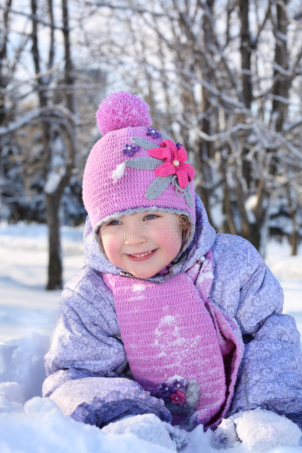 Den lyckliga lilla flickan i rosa halsduk och hatt ligger i snö royaltyfri fotografi