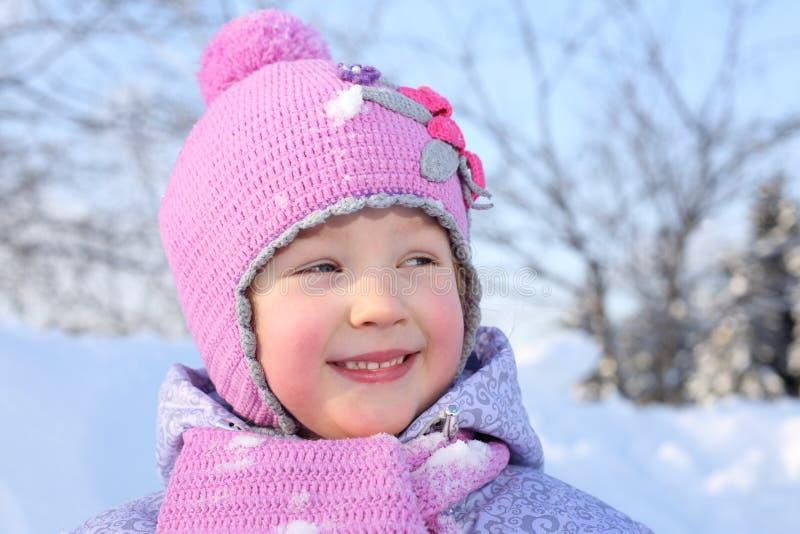 Den lyckliga lilla flickan i rosa halsduk och hatt ser fotografering för bildbyråer