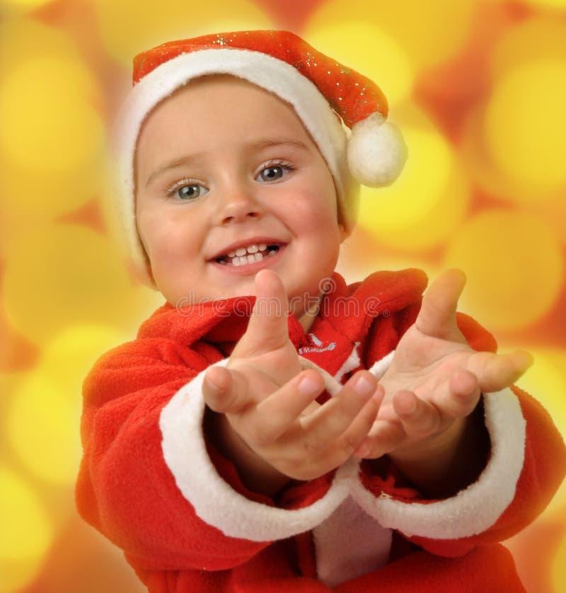 Den lyckliga lilla flickan i santa den röda hatten har jul arkivfoton