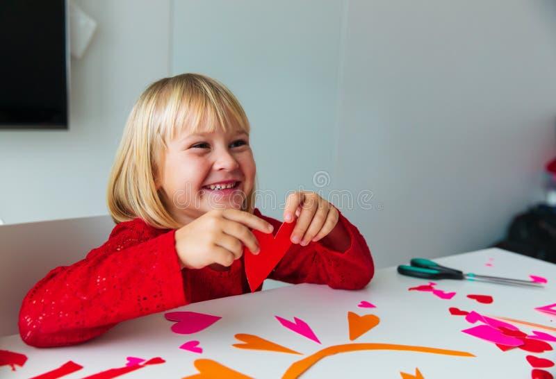 Den lyckliga lilla flickan klippte hjärtor från papper förbereder sig för valentindag royaltyfria bilder