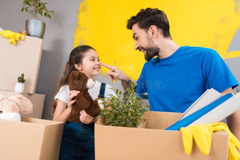 Den lyckliga lilla flickan med asken av flotta leksaker ser fadern som startade reparation i hus royaltyfria bilder