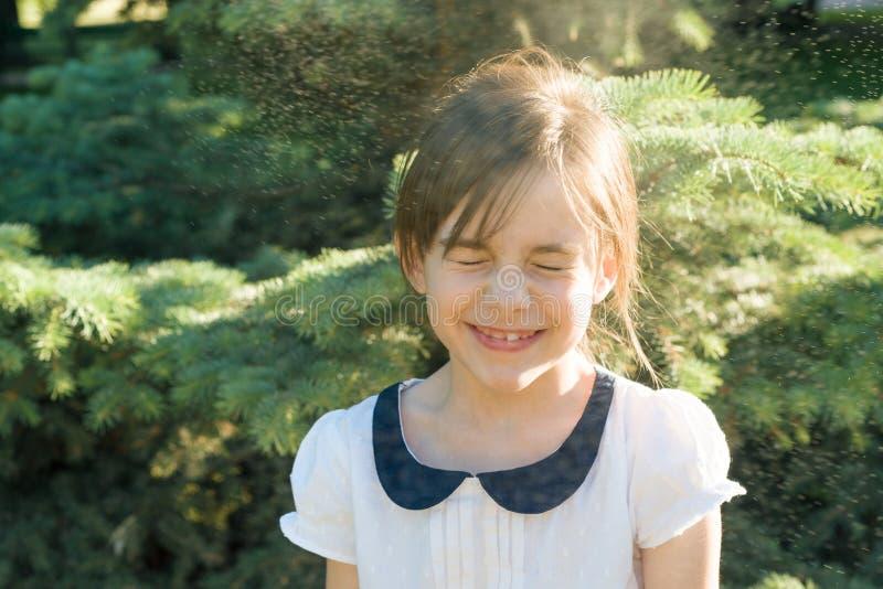 Den lyckliga lilla flickan med stängda ögon i sprej av termiska vattendroppar på varm sommardag i parkerar fotografering för bildbyråer
