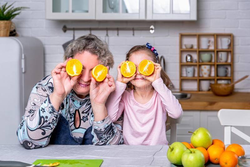 Den lyckliga lilla flickan och hennes farmor har frukosten tillsammans i ett vitt k?k De har gyckel och spelar med frukter arkivfoton