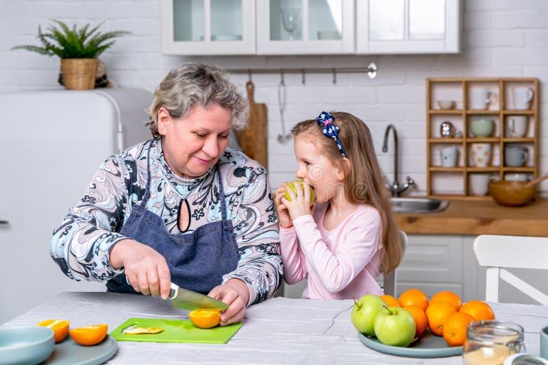 Den lyckliga lilla flickan och hennes farmor har frukosten tillsammans i ett vitt k?k De har gyckel och spelar med frukter fotografering för bildbyråer