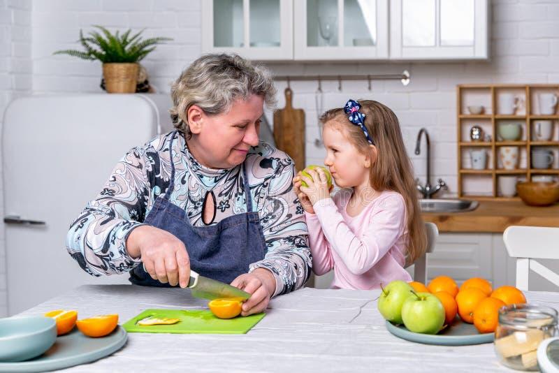 Den lyckliga lilla flickan och hennes farmor har frukosten tillsammans i ett vitt k?k De har gyckel och spelar med frukter royaltyfria foton