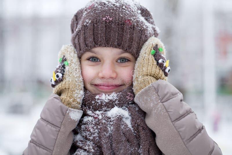Den lyckliga lilla flickan på bakgrunden av en vinter parkerar fotografering för bildbyråer