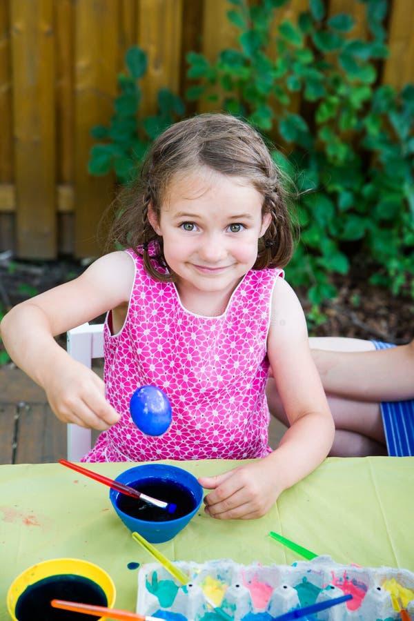Den lyckliga lilla flickan poserar med det färgade blåa påskägget arkivfoto