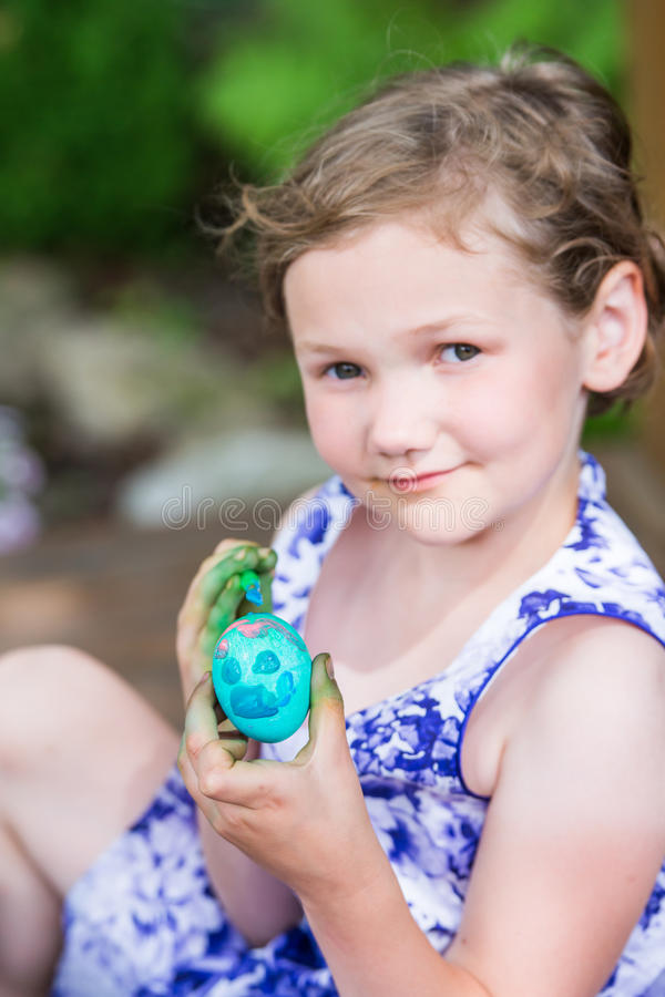 Den lyckliga lilla flickan poserar med det målade påskägget fotografering för bildbyråer