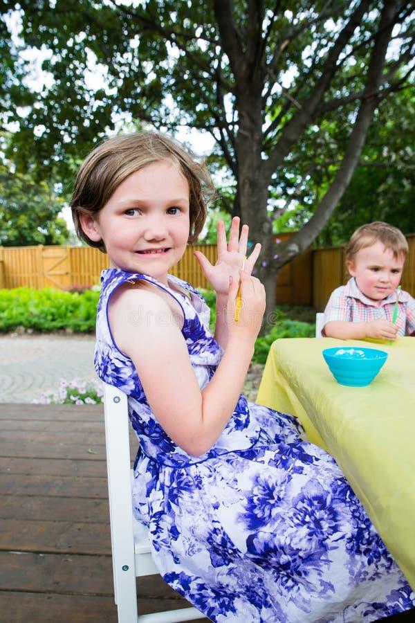Den lyckliga lilla flickan poserar med en målarfärgborste royaltyfri bild