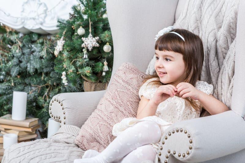 Den lyckliga lilla flickan sitter bekvämt i en ljus beigahemstol royaltyfria foton