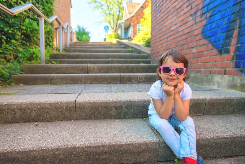 Den lyckliga lilla flickan sitter på kanten av en gränd arkivfoton