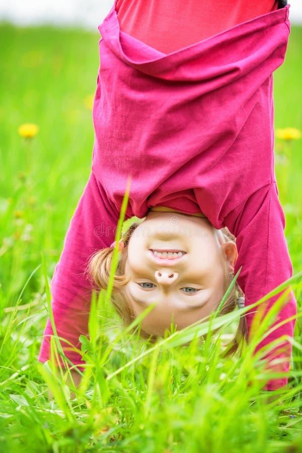 Den lyckliga lilla flickan som står uppochnervänd på gräs i sommar, parkerar royaltyfria foton