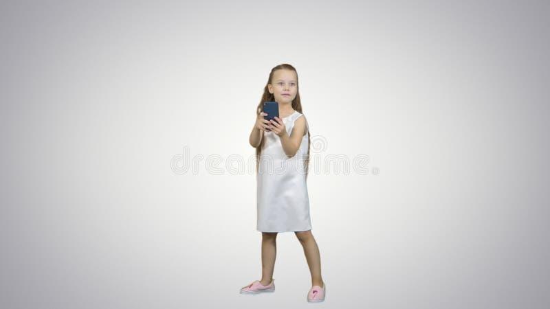 Den lyckliga lilla flickan tar en selfie med en smart telefon på vit bakgrund arkivbild