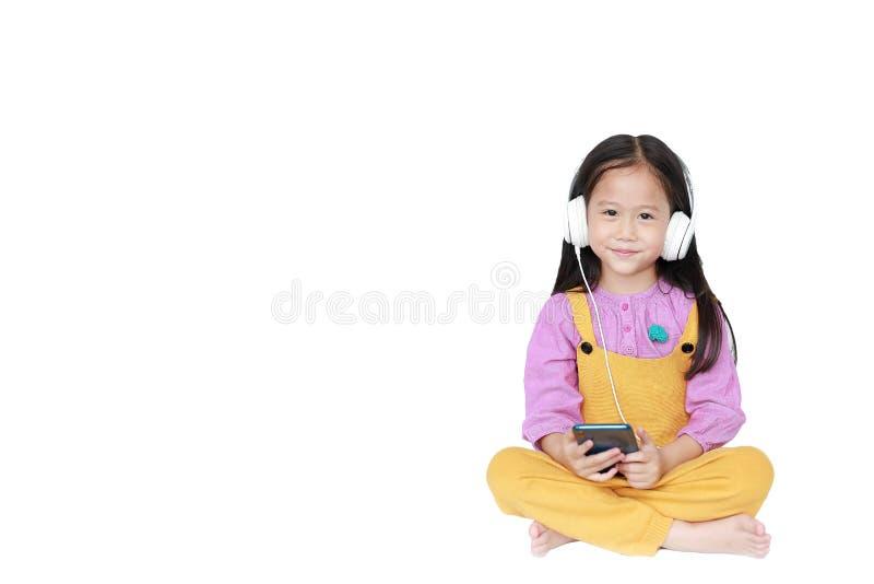 Den lyckliga lilla flickan tycker om att lyssna till musik med hörlurar som isoleras på vit bakgrund med kopieringsutrymme arkivbild