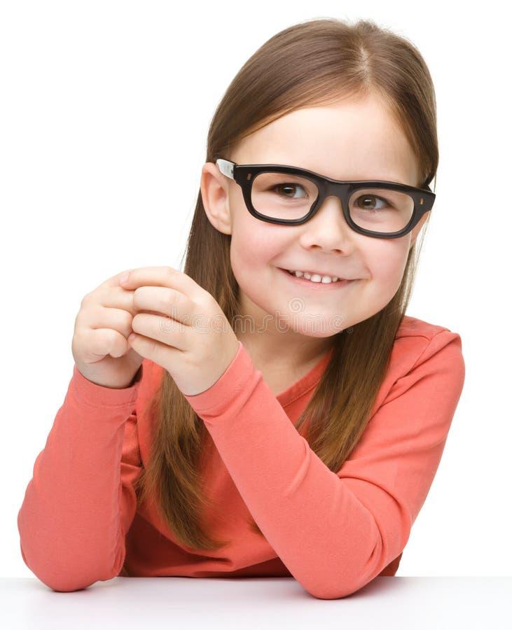 Den lyckliga liten flicka sitter på en tabell och ett leende royaltyfria bilder