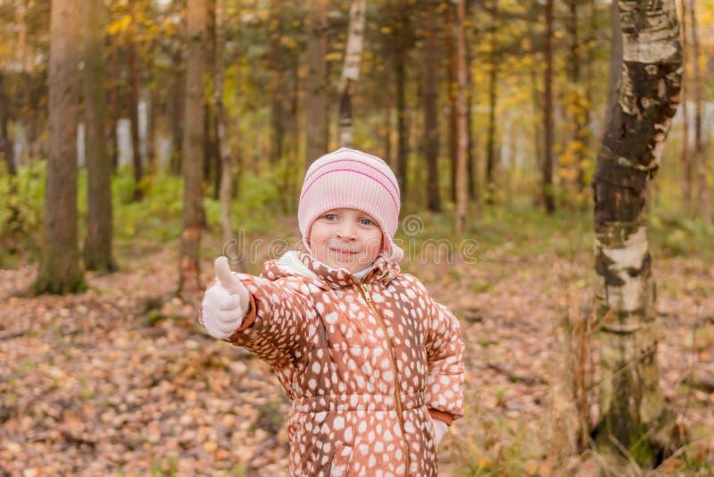 Den lyckliga liten flickavisningen tummar upp i solig dag på höstbakgrund Guld- höstträd och sjö Hösten landskap royaltyfria bilder