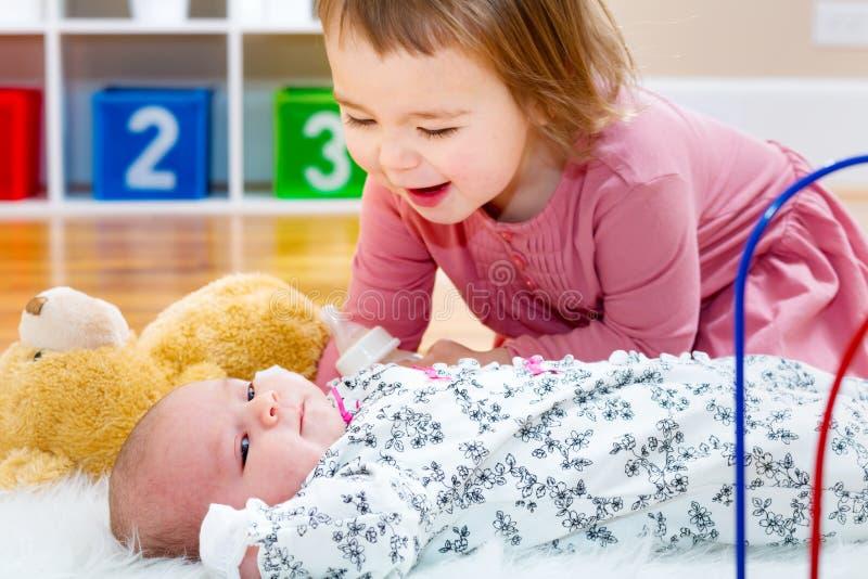 Den lyckliga litet barnflickan som spelar med henne, behandla som ett barn siblingen arkivbild