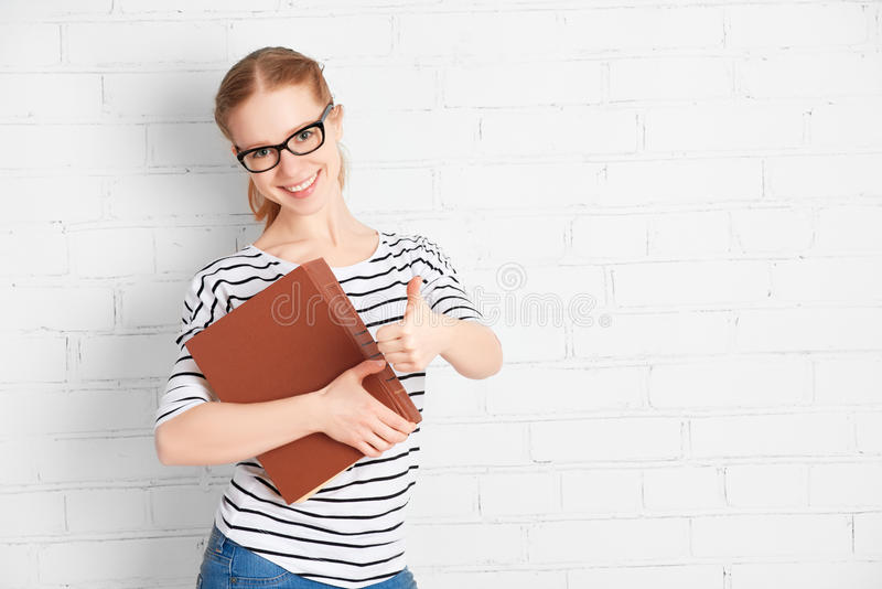 Den lyckliga lyckade studentflickan med bokvisning tummar upp royaltyfri foto
