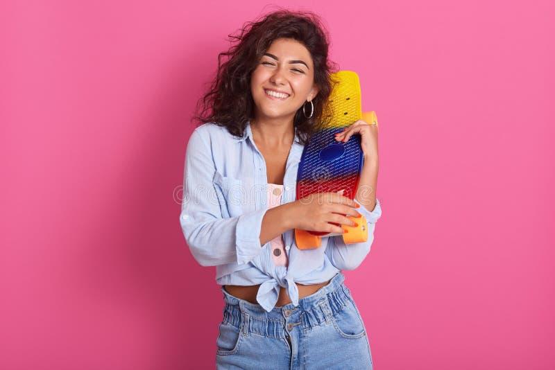 Den lyckliga mörka haired kvinnlign tycker om extrem ridning på skateboarden, har lockigt hår som rymmer brädet i händer, blickar arkivfoton