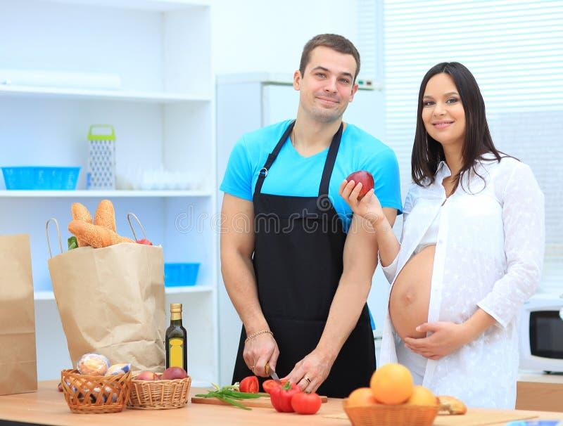 Den lyckliga maken gör frukosten för hans gravida fru arkivfoto