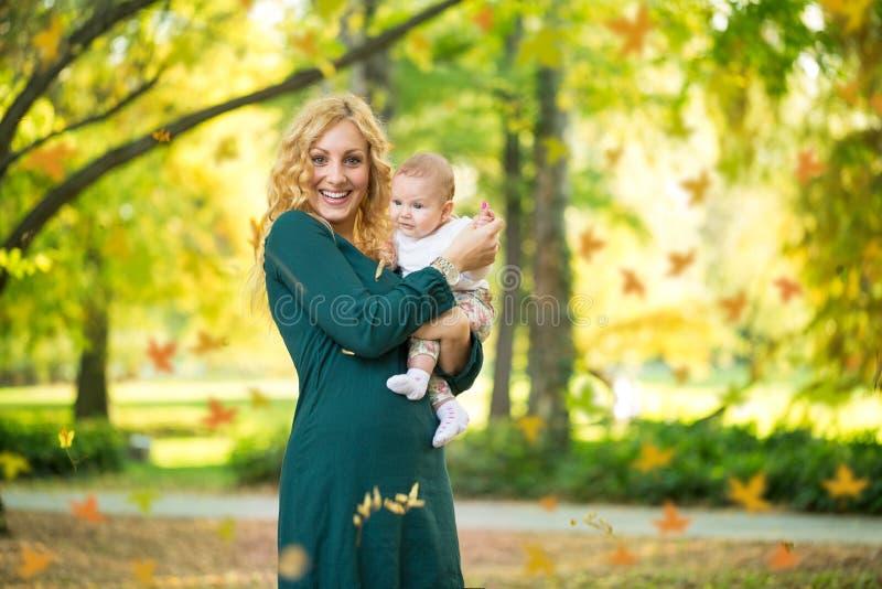 Den lyckliga mamman med behandla som ett barn royaltyfri fotografi