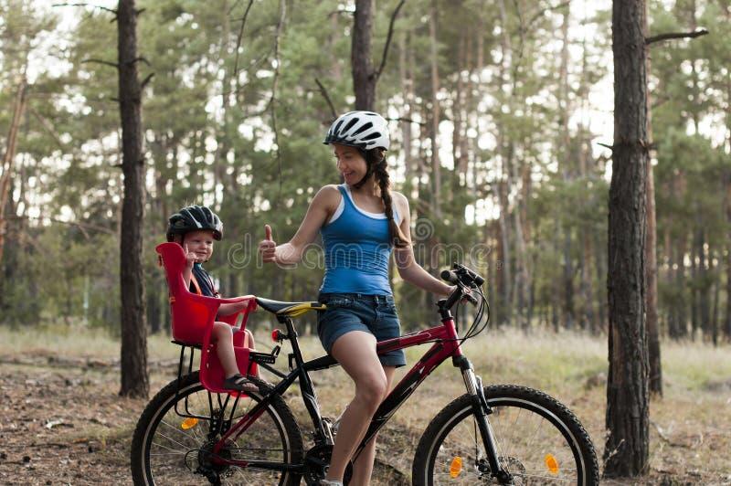 Den lyckliga mamman med den lilla sonen tyckte om ritt på cykeln arkivfoton